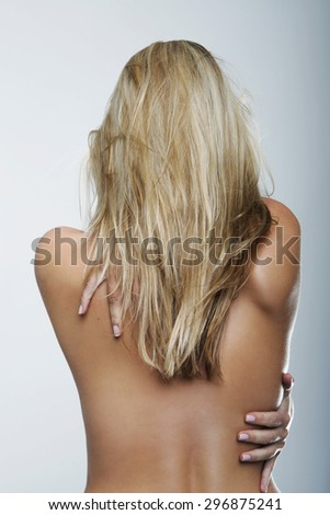 Half Body Rear View of a Bare Young Woman with Long Blond Hair, Reaching her Back Against Gray Wall Background. - stock photo
