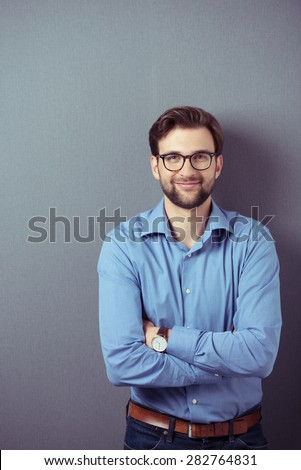 Half Body Shot of a Bearded Young Handsome Businessman Leaning Against Gray Wall with Arms Crossing Over his Stomach and Smiling at the Camera. - stock photo