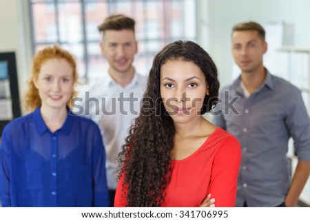 Half Body Shot of a Confident Office Woman Staring at the Camera Against Three Young Colleagues. - stock photo