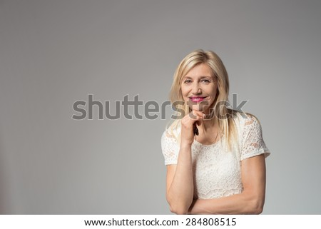Half Body Shot of a Confident Pretty Adult Woman with Blond Hair, With Hand on her Chin, Smiling at the Camera on a Gray Background with Copy Space - stock photo