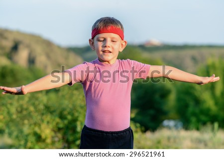 Half Body Shot of a Handsome Young Boy Raising his Arms While Practicing Martial Arts at the Field with Serious Facial Expression. - stock photo