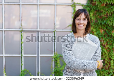 Half Body Shot of a Happy Businesswoman Hugging Newspaper and Smiling at the Camera Against Building Background - stock photo