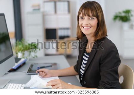 Half Body Shot of a Happy Businesswoman Working on Business Documents at her Table, Smiling at the Camera.