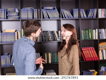 Half Body Shot of a Happy Young Couple Talking Inside the Mini Library While Facing Each Other. - stock photo