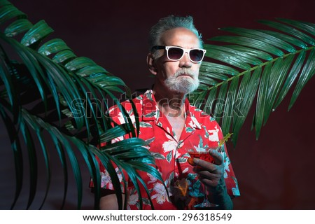 Half Body Shot of a Middle Aged Bearded Man in Beach Outfit with Sunglasses, Holding a Drink Between Palm Plants During a Night Party - stock photo