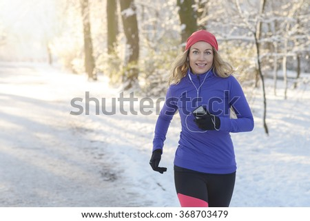 Half Body Shot of a Pretty Athletic Woman Jogging in winter with earphones and winter attire, Smiling at the Camera, with copy space - stock photo