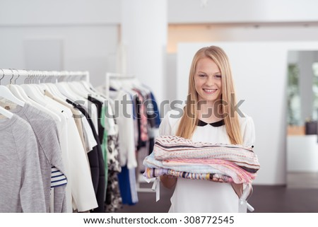 Half Body Shot of a Pretty Blond Girl Smiling at the Camera While Holding Some Folded Clothes Inside a Department Store - stock photo