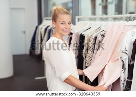 Half Body Shot of a Pretty Blond Woman Smiling at the Camera While Looking For Clothes inside a Fashion Store - stock photo