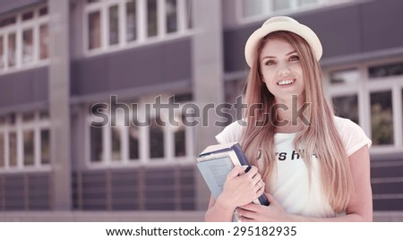 Half Body Shot of a Pretty Blond Young Student Holding Books, Smiling at the Camera Against the University. - stock photo