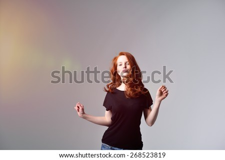 Half Body Shot of a Pretty Red Haired Woman in Motion, Wearing Black Shirt with Pouting Lips, Looking at the Camera on Gray Background. - stock photo