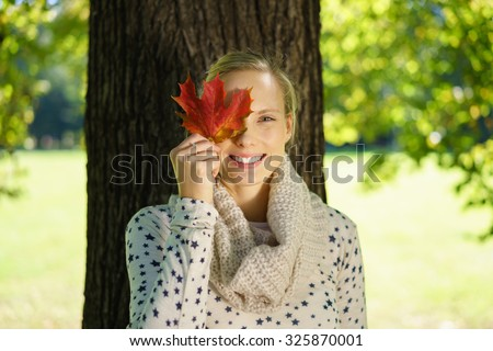 Half Body Shot of a Pretty Young Woman Holding an Autumn Leaf Over her Eye and Smiling at the Camera Against Huge Tree Trunk at the Park.