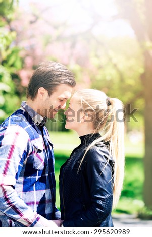 Half Body Shot of a Romantic Young Couple at the Park, Smiling to Each Other So Close on A Very Sunny Day. - stock photo