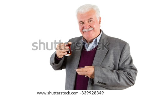 Half Body Shot of a Senior Businessman Holding a Glass of Turkish Tea and Smiling at the Camera Against White Background. - stock photo