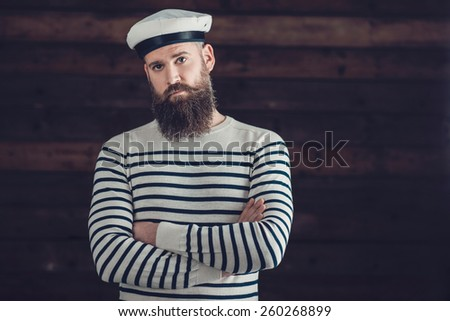 Half Body Shot of a Serious Man with Long Beard Wearing Trendy Black and White Stripe Shirt and Sailor Hat Attire, Crossing his Arms While Looking at the Camera. - stock photo