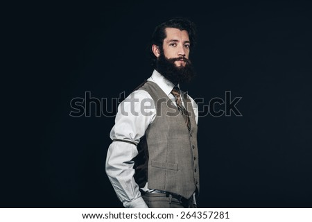 Half Body Shot of a Young Man with Long Goatee Beard, Wearing Formal Attire with Vest, Looking at the Camera. Isolated on Black Background. - stock photo
