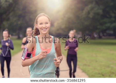 Half Body Shot of an Athletic Pretty Young Woman Smiling at the Camera While Jogging at the Park with Other Girls, with copy space on the right - stock photo