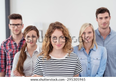 Half Body Shot of Five Young Business People in Casual Clothing Inside the Office, with Young Female Leader, Smiling at the Camera - stock photo