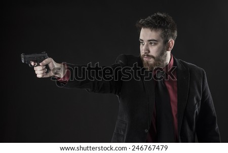 Half Body Shot of Goatee Young Man in Black Suit Aiming a Small Gun in Side View. Isolated on Black Background - stock photo