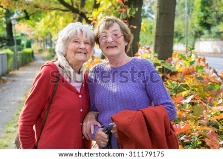 Half Body Shot of Two Happy Middle Aged Women in Autumn Outfits at the Pathway  Smiling at the Camera. - stock photo