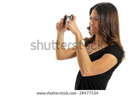 Half body view of attractive brunette shooting with small camera. Isolated on white background.