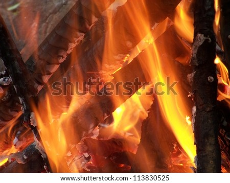 Half burned wooden sticks covered with flames in the campfire