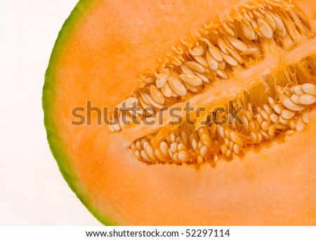 half cantaloupe showing seeds, flesh and rind, isolated on white background - stock photo