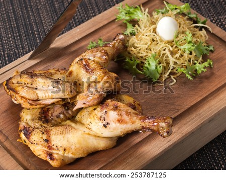 half chicken marinated in plum wine on wooden board with herbs - stock photo