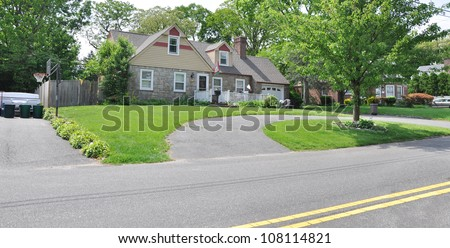 Half Circle Blacktop Driveway Suburban Stone Home in Residential Neighborhood along street with double yellow traffic dividing lines