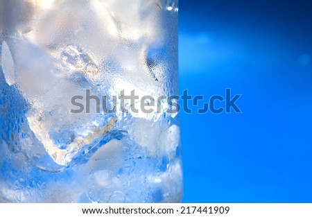 half close up a glass of ice cubes with half blue background - stock photo