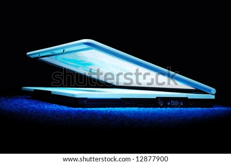 Half-closed silver laptop with blue bright screen - stock photo