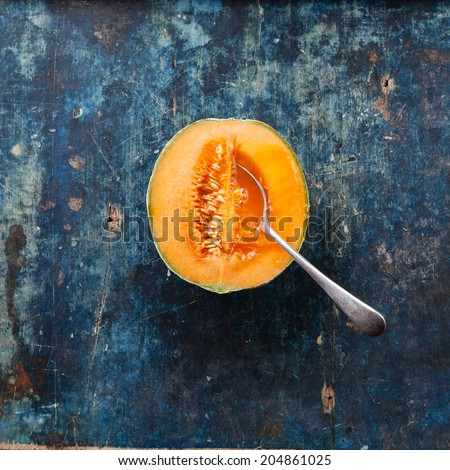 Half cut of ripe cantaloupe melon with spoon on blue background - stock photo