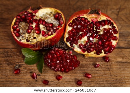 Half-cutted fresh pomegranates on rustic wooden table - stock photo