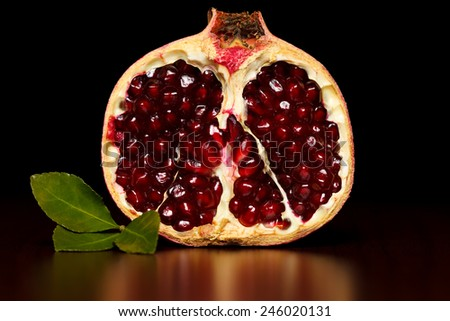 Half-cutted pomegranate with green leaf over dark background - stock photo