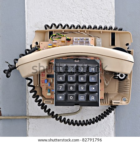 half dismounted old phone hanging on the wall - stock photo