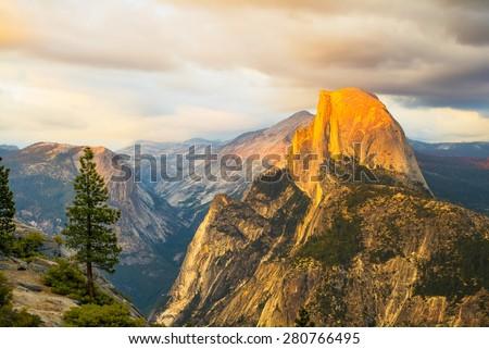 Half Dome Rock Yosemite National Park at Sunset.  A lone tree at Half Dome Rock. - stock photo