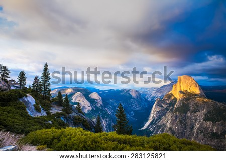 Half Dome Rock Yosemite National Park at Sunset.  Forest in foreground. - stock photo