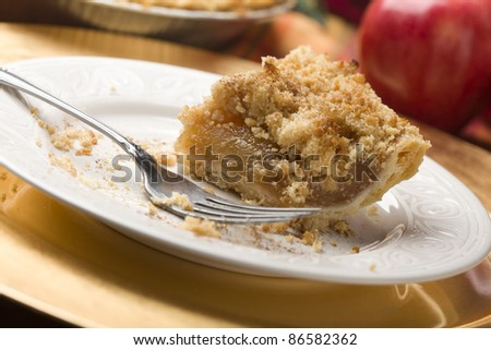 Half Eaten Apple Pie Slice with Crumb Topping and Fork.