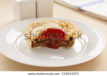 Half eaten meat pie with ketchup dripping down the front.