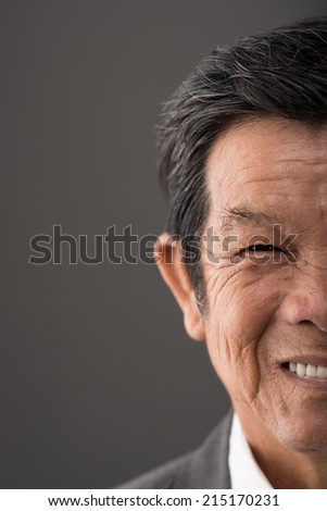Half face close up portrait of senior Vietnamese man