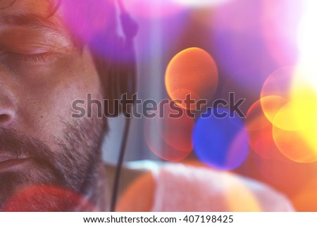 Half face low key portrait of adult unshaven man listening to music on headphones with his eyes closed, enjoying favorite song, nice bokeh light - stock photo