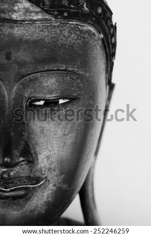 Half Face of a Buddha Statue Isolated on a White Background - stock photo