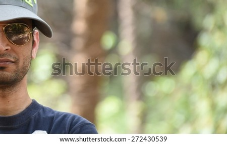 Half face of man wearing glasses with natural green blurred background, ample space for text - stock photo