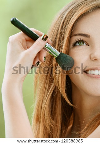 Half face of miling beautiful young woman with bare shoulders on face powder, against green of summer park. - stock photo
