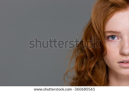 Half face of redhead attractive curly young woman with beautiful long hair over grey background - stock photo