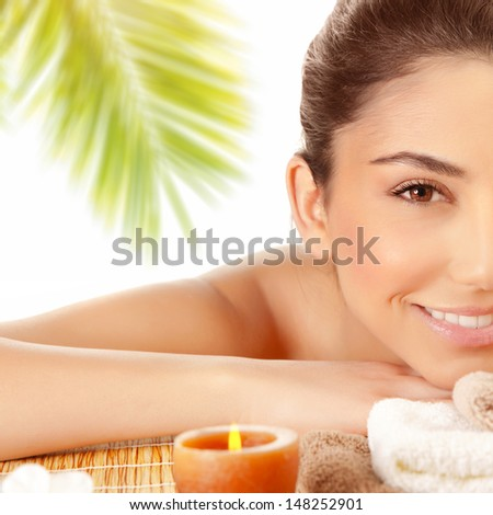 Half face of sexy brunette girl enjoying day spa on massage table outdoors, exotic beach resort, palm trees, well being and pleasure concept  - stock photo