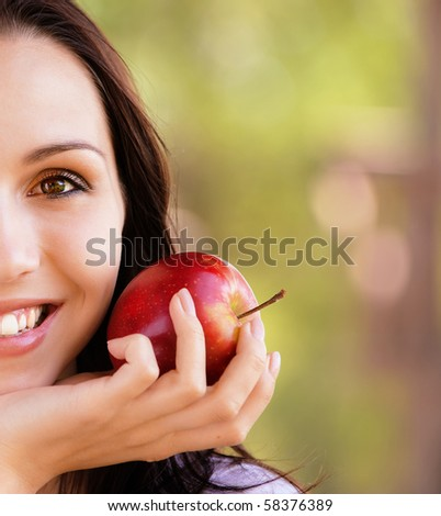 Half face of smiling young woman with red apple - stock photo