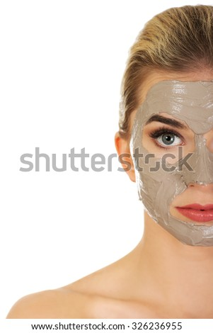 Half face of young woman with facial mask, isolated on white.