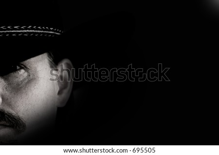 Half-face portrait of a cowboy in black hat against black background with shadow and light effect.