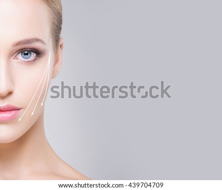 Half face portrait of attractive girl with beautiful blue eyes and arrows on face over grey background. Face lifting concept. - stock photo
