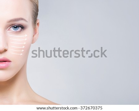 Half face portrait of beautiful, healthy woman over grey background. Face lifting concept. - stock photo